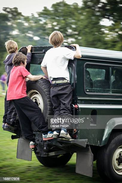 CONTENT] Three teenage boys standing on the back bumper of a moving off road vehicle in a field
