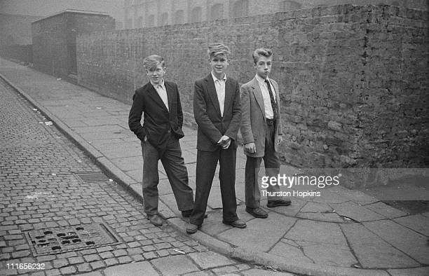 Three teenage boys with fashionable hairstyles on a street corner in a slum area of Liverpool 19th November 1956 Original publication Picture Post...