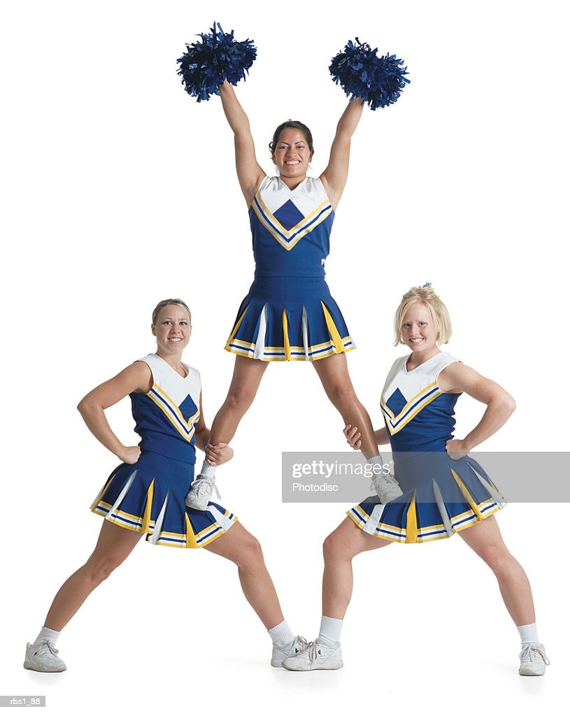 three teenage caucasian female cheerleaders in blue uniforms cheer as they form a small pyramid : Foto de stock