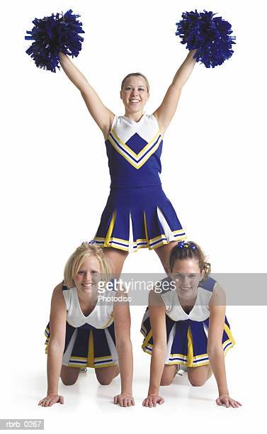 three teenage caucasian female cheerleaders in blue uniforms pose making a pyramid with the top girl holding pom-poms