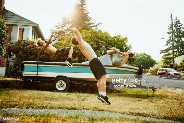 Three teenage friends doing backflips in front yard on summer evening