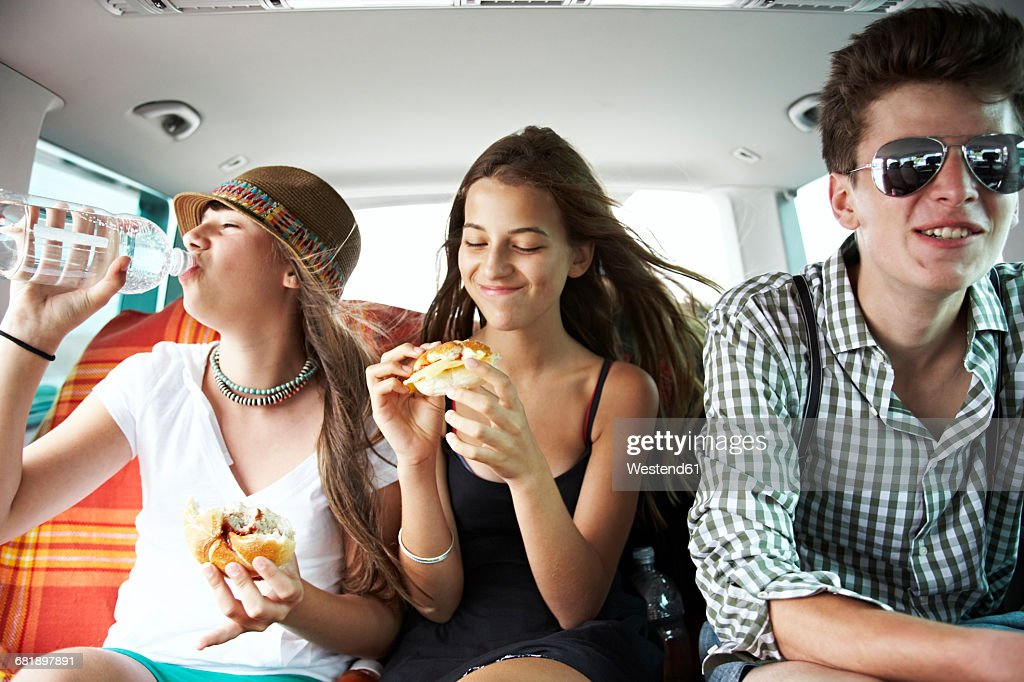Three teenage friends having a snack in car : Stock Photo