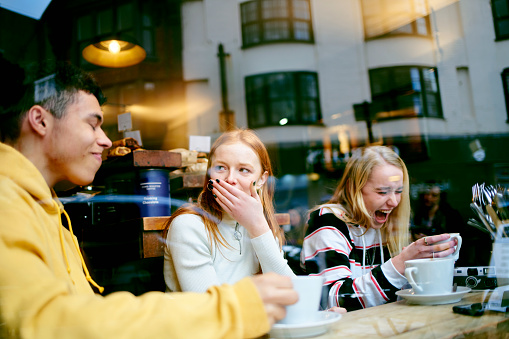 Three teenage friends in a cafe enjoying a joke, sharing a moment and having fun while drinking coffee - gettyimageskorea