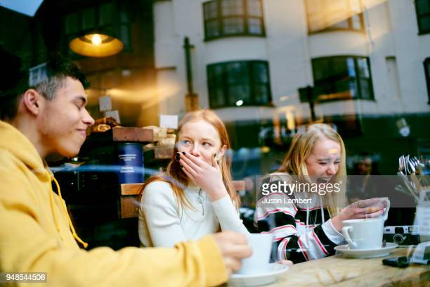 Three teenage friends in a cafe enjoying a joke, sharing a moment and having fun while drinking coffee
