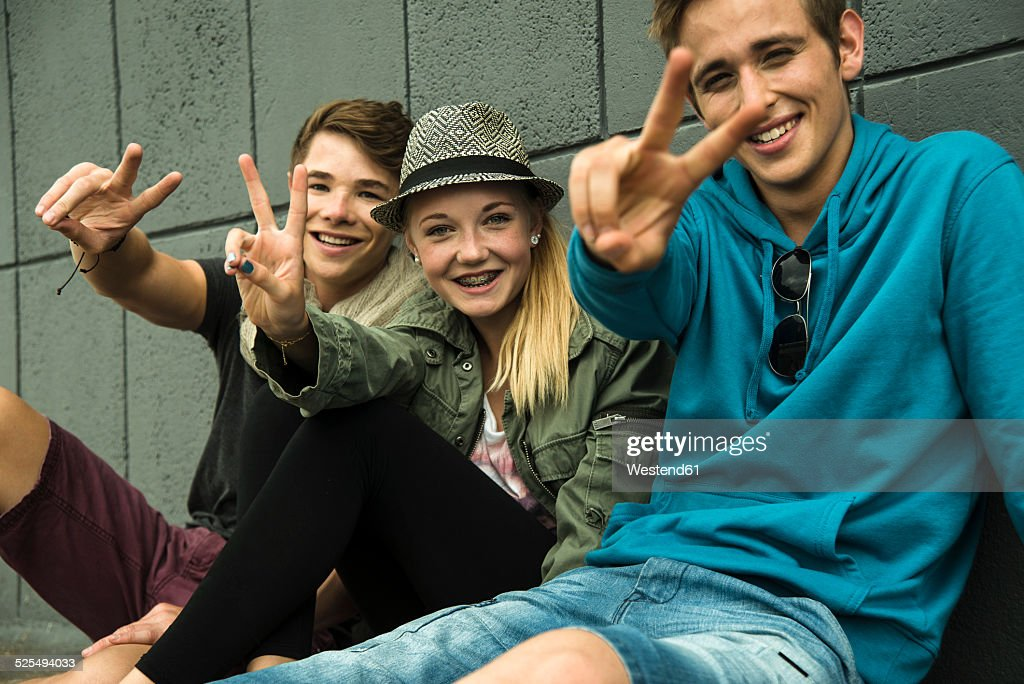 Three teenage friends making peace hand sign : Stock-Foto