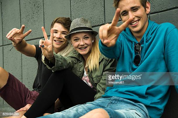 three teenage friends making peace hand sign - jugendliche stock-fotos und bilder