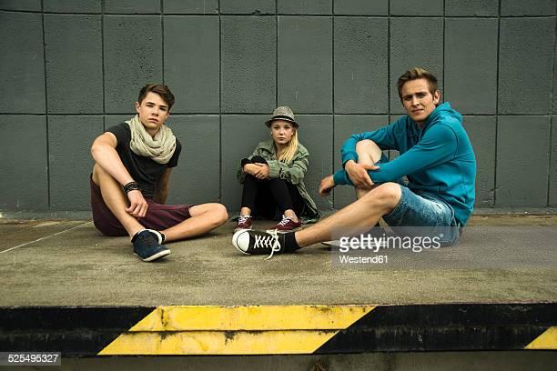 Three teenage friends sitting outdoors