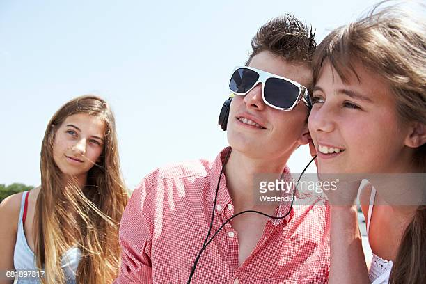 Three teenage friends with headphones outdoors