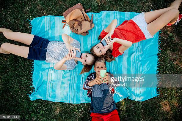 Three teenage friends with smartphones lying on blanket