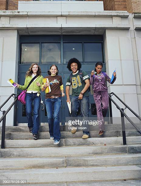 Three teenage girls and teenage boy (13-16) walking down school steps, smiling