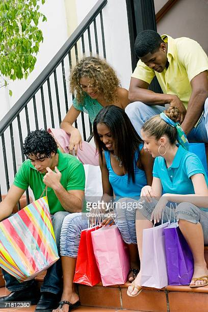 three teenage girls and two young men sitting on steps and looking into shopping bags - girl wear jeans and flip flops stock photos and pictures