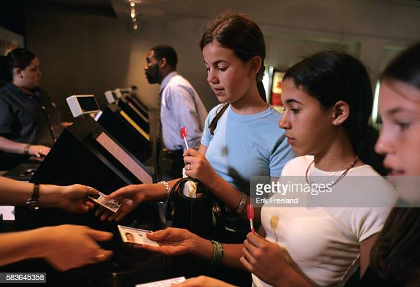 Three teenage girls are asked for identification before they are sold tickets to a PG13 movie at AMC Theater in Manhattan