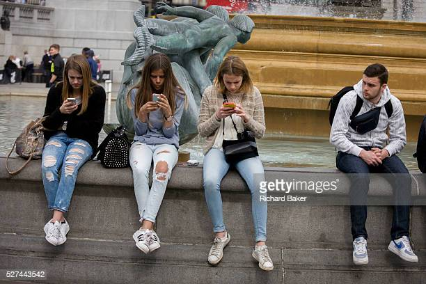 Three teenage girls are lost in the world of smartphone apps and messaging in Trafalgar Square While in a very busy environment in the capital's main...