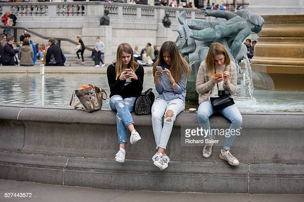 Three teenage girls are lost in the world of smartphone apps and messaging in Trafalgar Square While in a very busy environment the capital's main...