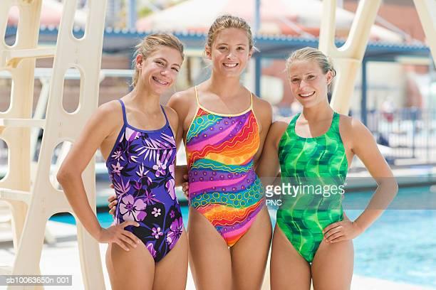 Three teenage girls (16-18) at swimming pool, portrait