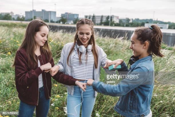 three teenage girls bumping fists outdoors