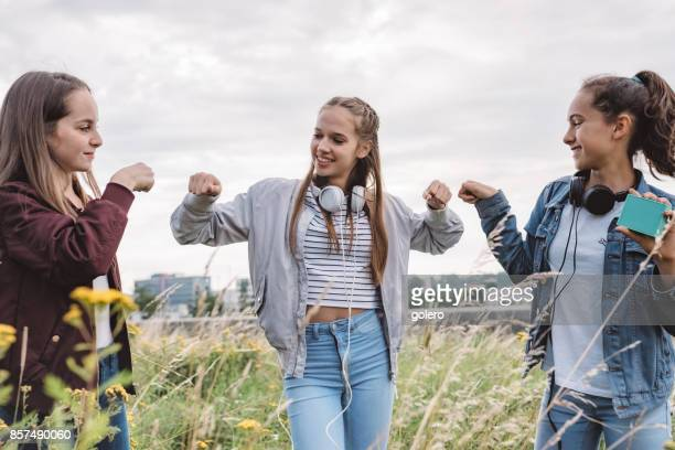 three teenage girls doing fist bump outdoors - fist bump stock pictures, royalty-free photos & images