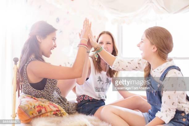 Three teenage girls doing high five on bed