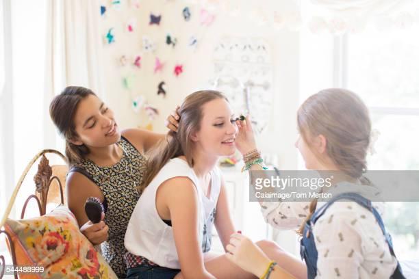 Three teenage girls doing make up and brushing hair in bedroom