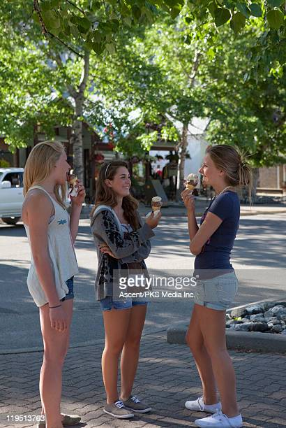Three teenage girls eat ice cream, village street