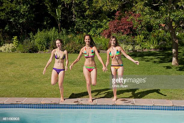 three teenage girls in bikinis in outdoor pool - swimwear stock photos and pictures