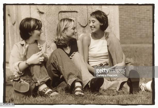 Three teenage girls (13-16) laughing outdoors (toned B&W)
