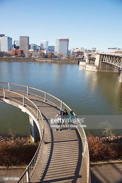 Three Teenage Girls On A Pedestrian Bridge Over A River