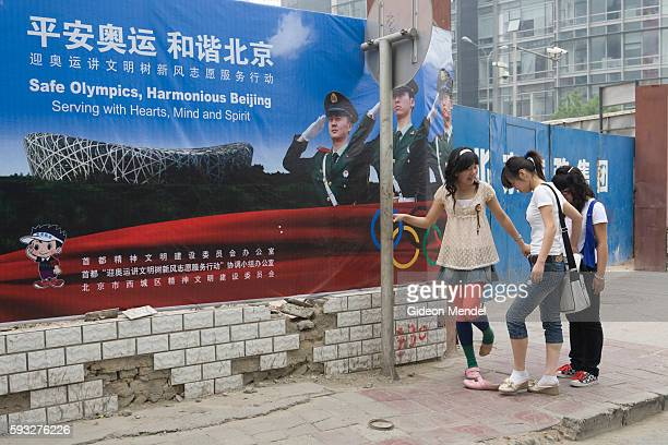 Three teenage girls pause to correct their shoes in the Xidan shopping area unaware of the disconcerting scene created by the huge image of soldiers...