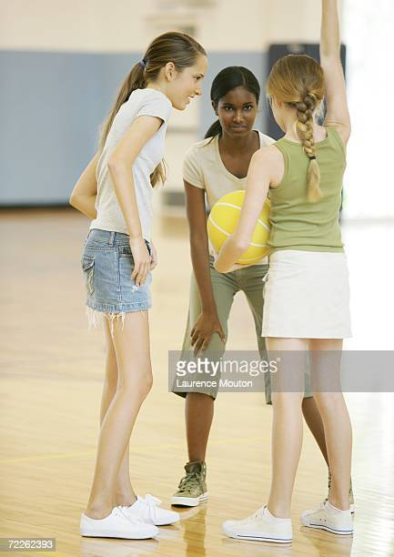 three teenage girls playing basketball in school gym - ado minijupe photos et images de collection