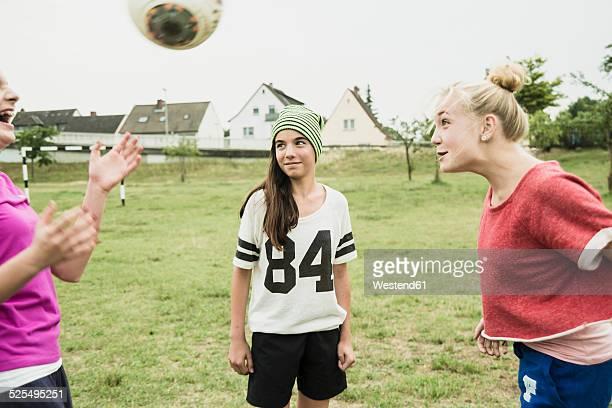 Three teenage girls playing soccer on a football ground