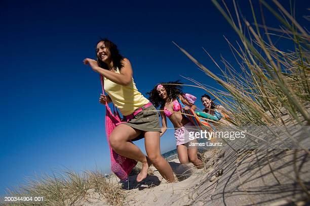 three teenage girls (14-17) running in sand dune, smiling - ado minijupe photos et images de collection