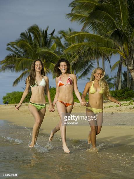Three teenage girls running on the beach