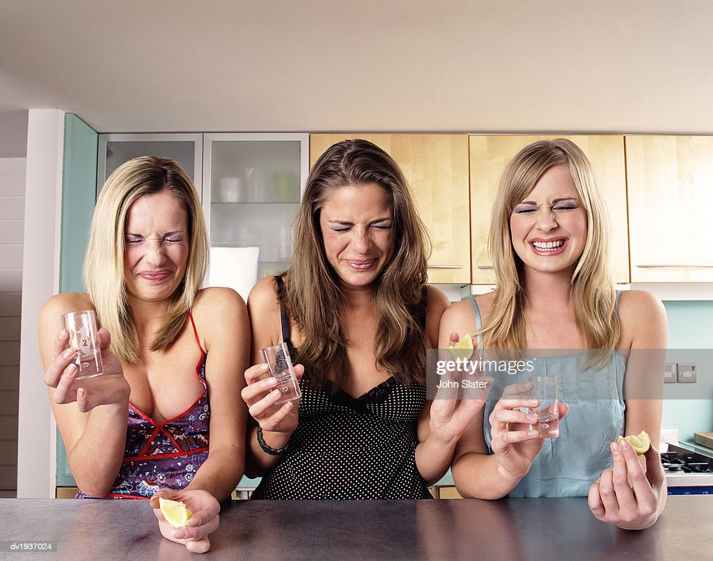 Three Teenage Girls Sit at a Kitchen Counter Grimacing After Drinking a Shot of Tequila : Stock Photo