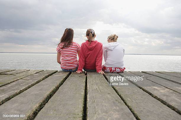three teenage girls (12-13) sitting on wooden pier, rear view - southend on sea stock pictures, royalty-free photos & images