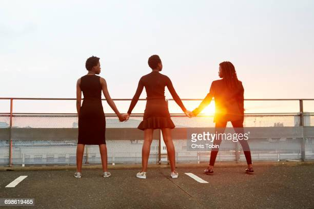 Three teenage girls standing hand in hand