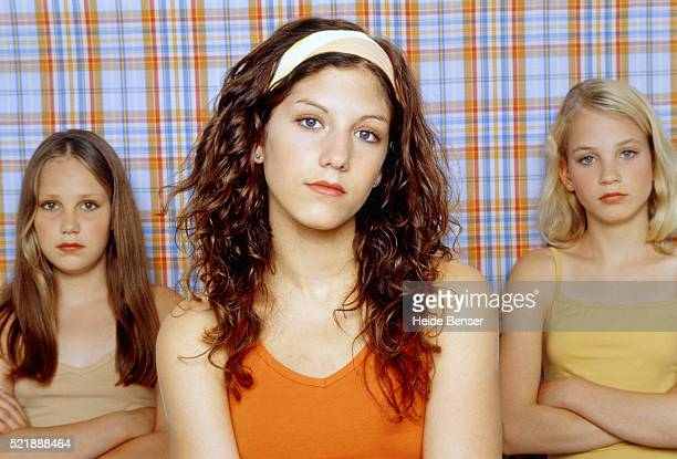 Three teenage girls standing in front of checked wallpaper