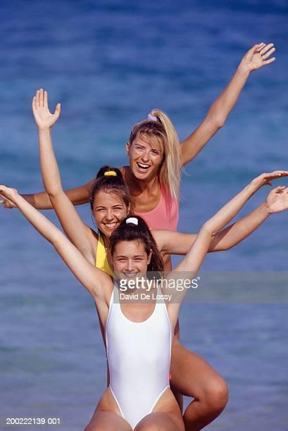 Three teenage girls (13-14) standing in line at seaside, portrait