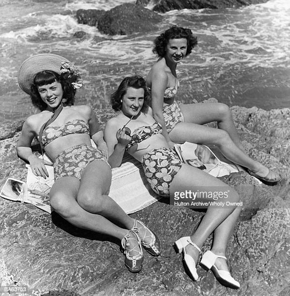 Three teenage girls (16-18) sunbathing on rocks, portrait (B&W)