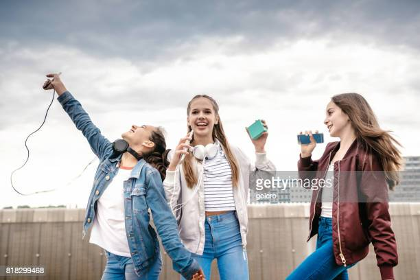three teenage girls taking cheering outdoors - bluetooth stock pictures, royalty-free photos & images