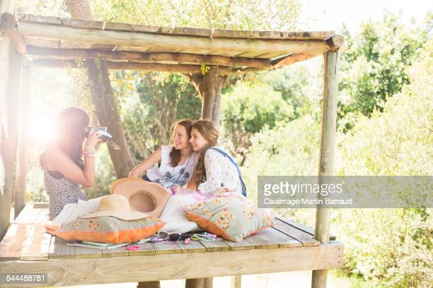 Three teenage girls taking photos in tree house in summer