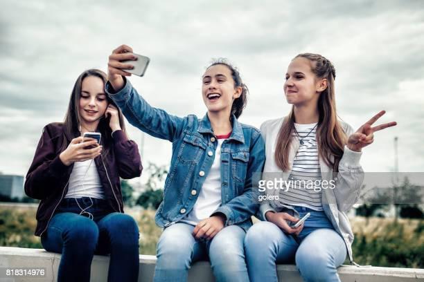 drei Mädchen im Teenageralter unter Selfie im freien