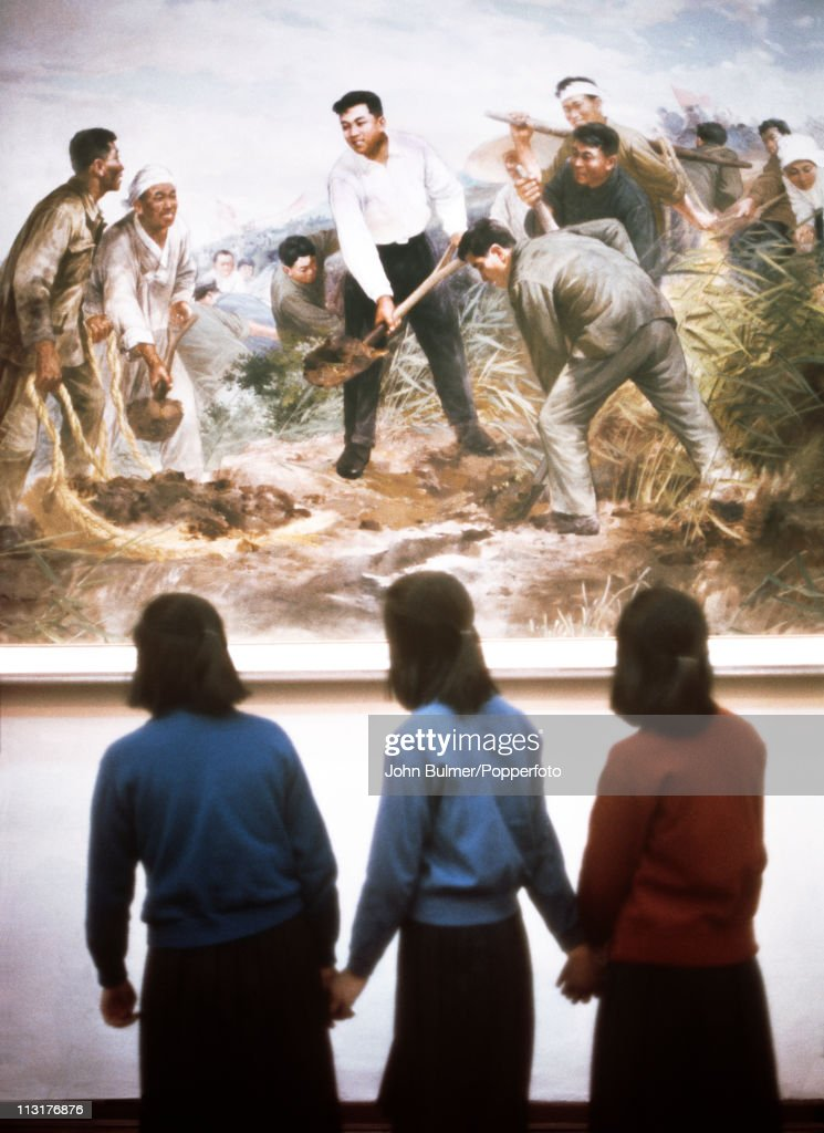 Three teenage girls viewing a painting in a museum in North Korea, February 1973.