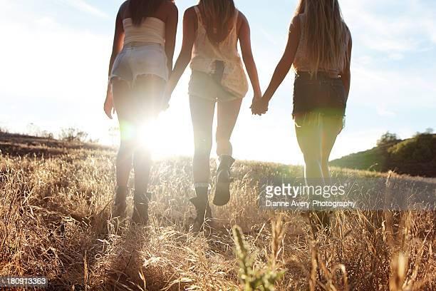 Three teenage girls walking in sunset-shorts boots