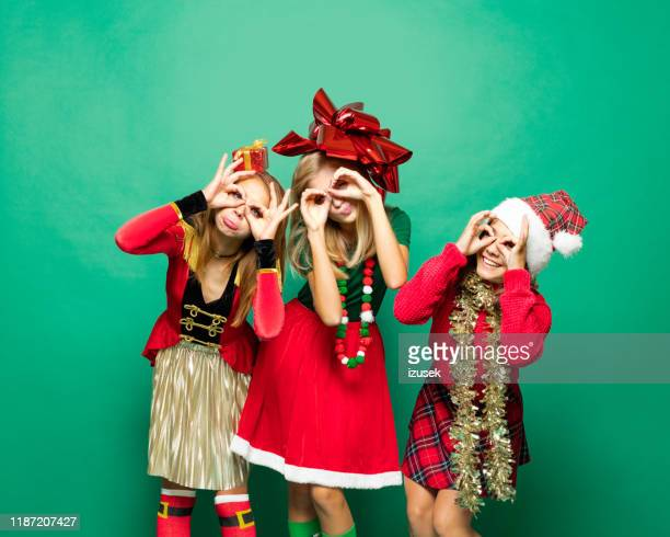 three teenage girls wearing christmas clothes making funny faces - izusek stock pictures, royalty-free photos & images