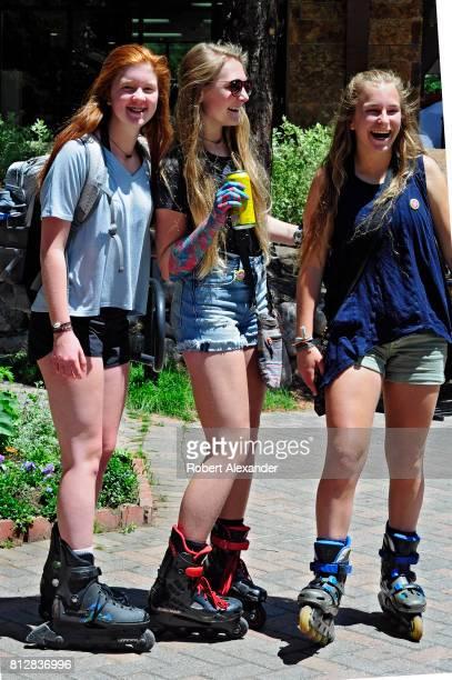 Three teenage girls wearing roller blades enjoy themselves in Vail Colorado