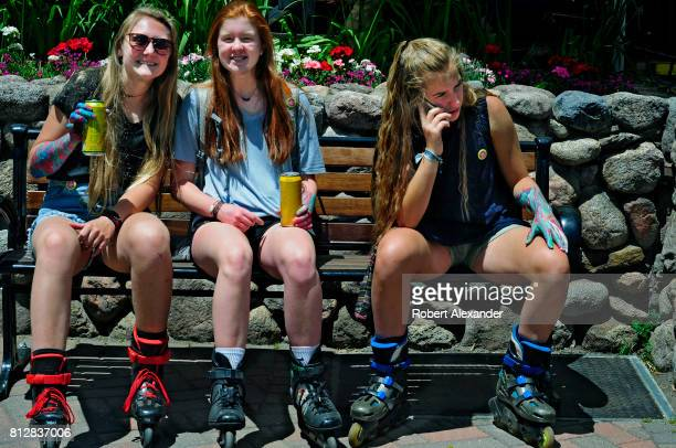 Three teenage girls wearing roller blades sit on a bench in Vail Colorado