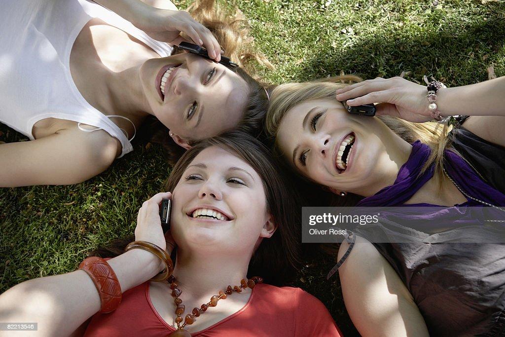 Three teenage girls with mobile phones : Stock Photo