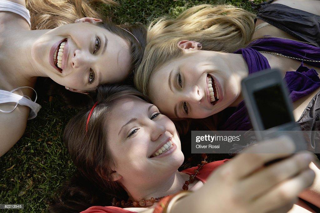 Three teenage girls with mobile  : Stock Photo
