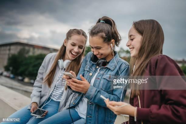 drie tienermeisjes met smartphones outdoors - pubertijd stockfoto's en -beelden
