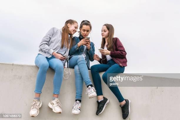 drei mädchen im teenageralter mit smartphones auf mauer sitzend - jugendkultur stock-fotos und bilder